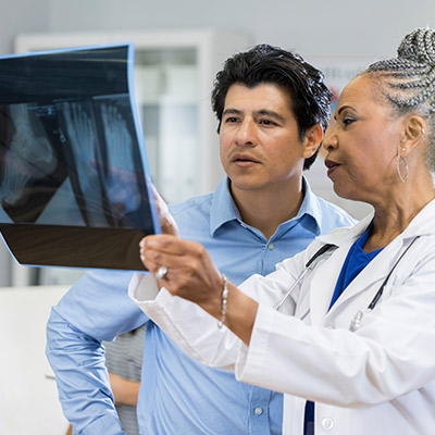 Specialist reviewing an x-ray with a patient.